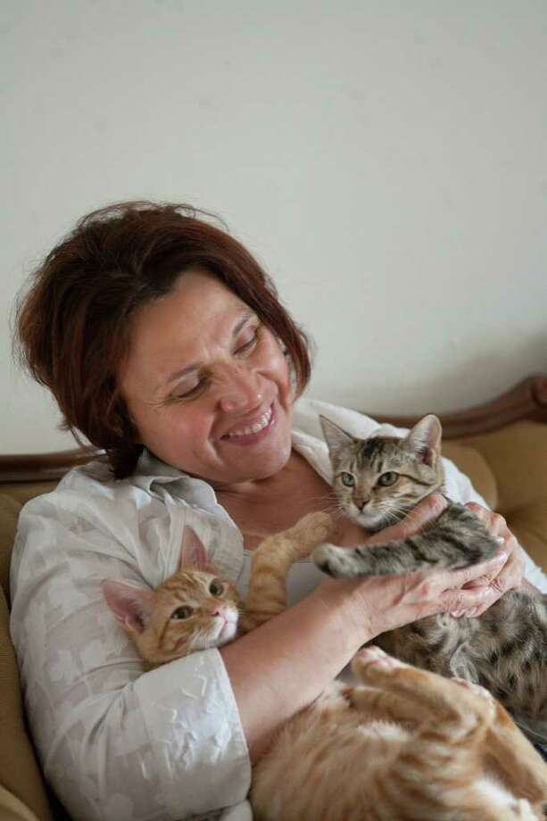 Sandy Luna plays with her two new kittens, Paco and Lola. (Paco's the ginger boy.) Luna acquired the kittens after her cat Lucky was killed last month; she says they're indoor cats for their own safety.  Photo by R. Clayton McKee Photo: R. Clayton McKee, Freelance / © R. Clayton McKee