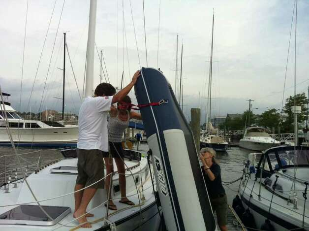 "Jay and Carolee Gravina take the inflatable dinghy off the foredeck of their 25-foot sailboat ""Faith"" on Thursday, August 25, 2011 at Brewer Yacht Haven Marina in Stamford, Conn. The Gravinas were among the boaters throughout New England preparing for the potential arrival of Hurricane Irene. Photo: John Nickerson"