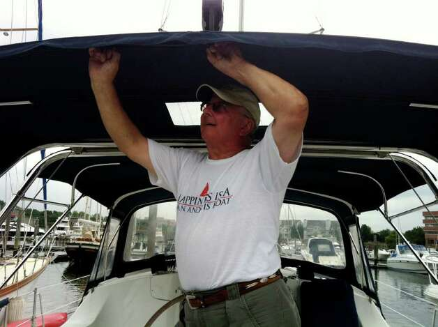 "Frank Cook wearing a T-shirt saying ""Happiness is a man and his boat"" adjusts the bimini aboard his 44-foot sailboat Mystic Blue II at Brewers Yacht Haven Marina East. A Yorktown Heights, N.Y., resident who was with his wife Janice were putting more lines and fenders out to prepare for Hurricane Irene. Photo: John Nickerson"