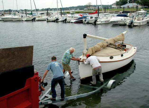 "Trying to keep ahead of Hurricane Irene, Tim Currier gets some help getting his granddaughter's sailboat ""Egg Roll"" out of the water at Longshore Marina in Westport, Conn. on Thursday Aug. 25, 2011. The storm is expected to hit the region over the weekend. Photo: Cathy Zuraw / Connecticut Post"