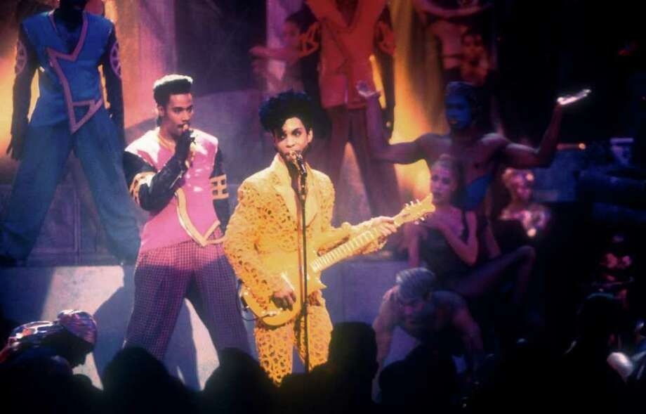 "1991: During his performance of ""Gett Off,"" Prince revealed a surprise to the audience: his bare bottom, exposed through a cut-out in the yellow costume.  Photo: Frank Micelotta, Getty Images / Getty Images North America"