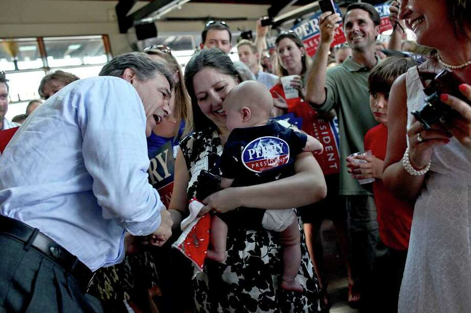 Governor Rick Perry greets Courtney Goodings, of Austin, and her four-month-old son, Callum Goodings, as Perry arrives for the Rick Perry Welcome Home Rally at Abel's on the Lake in Austin on Saturday, August 20, 2011. Photo: LISA KRANTZ, LISA KRANTZ/lkrantz@express-news.net / SAN ANTONIO EXPRESS-NEWS