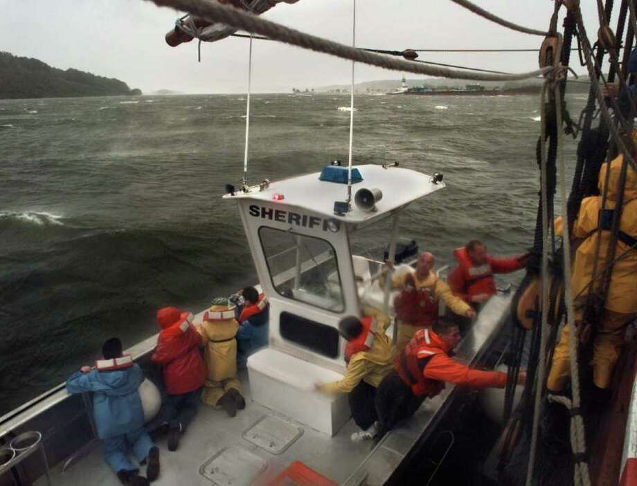 Coast Guard personnel aboard a Ulster County Sheriff's evacuate school children from the Half Moon on the Hudson River near Saugerties on Sept. 16, 1999, as the brunt of Hurricane Floyd  passed through the region. The 12 school students and three teachers were off loaded as a precautionary measure. (Paul Buckowski/Times Union archive) Photo: PAUL BUCKOWSKI / TIMES UNION