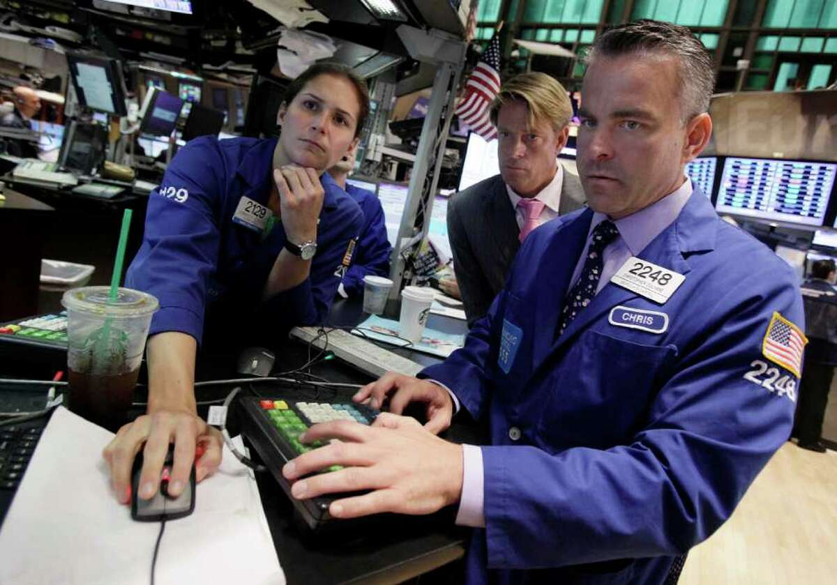 Specialists Jennifer Klesaris, Patrick Murphy, center, and Christopher Culhane work at the post that trades Citibank on the floor of the New York Stock Exchange Thursday, Aug. 25, 2011. (AP Photo/Richard Drew)