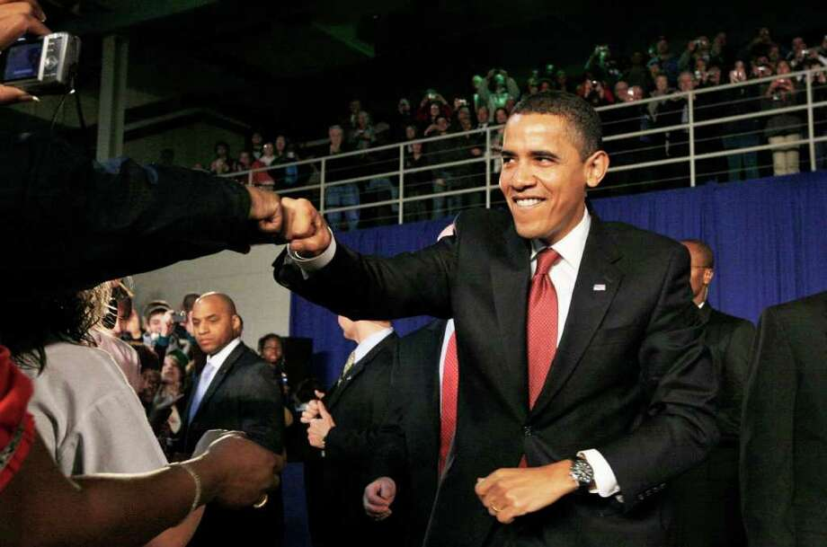 FILE - In this Feb. 9, 2009, file photo, President Barack Obama fist bumps with an audience member as he arrives for a town hall style meeting at Concord Community High School in Elkhart, Ind.  Though the knuckle-tapping action has been around for years, fist bump's place in popular culture was cemented by President Obama and First Lady Michelle Obama when Obama accepted the 2008 Democratic nomination, and now has earned a spot in the Merriam-Webster Collegiate Dictionary.  (AP Photo/Charles Dharapak, File) Photo: Charles Dharapak