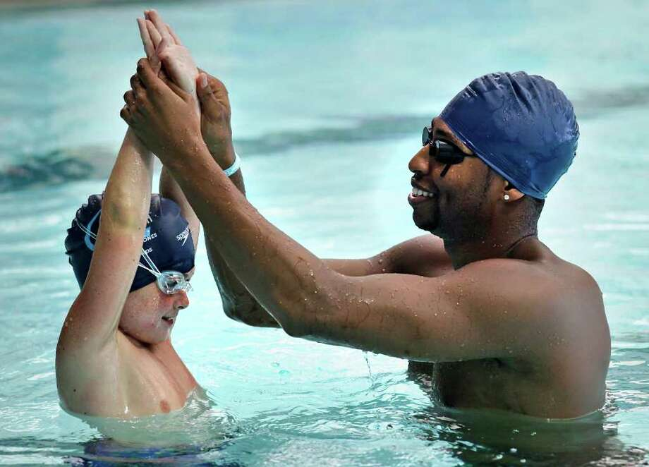 Olympic gold medalist Cullen Jones shows Ethan Grisham how to hold his hands to push off the side of the pool during a swimming lesson for a group of students from Serna Elementary School at the Josh Davis Natatorium. The event on Thursday, Aug. 25, 2011, was sponsored by the USA Swimming Foundation. Photo: Bob Owen/rowen@express-news.net / rowen@express-news.net