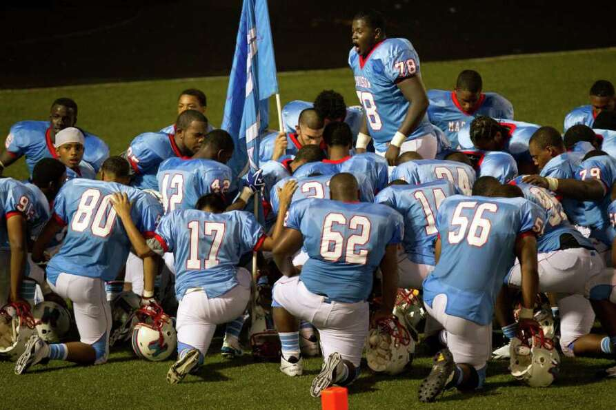 Madison players huddle around lineman Cleveland Sims (78) before taking the field against Pearland f