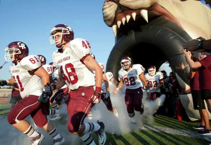 Cinco Ranch player run onto the field before facing Klein Forest at Klein Memorial Stadium.