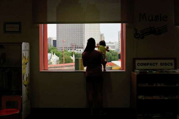 Erica Ramirez and her 15-month-old daughter Sophia Vela look out at downtown San Antonio from the Central Library at a rare sight this summer: rain. The temperature in the Alamo City is expected to reach 103 degrees today, 106 Saturday and 108 Sunday and Monday. Photo: Lisa Krantz/lkrantz@express-news.net / lkrantz@express-news