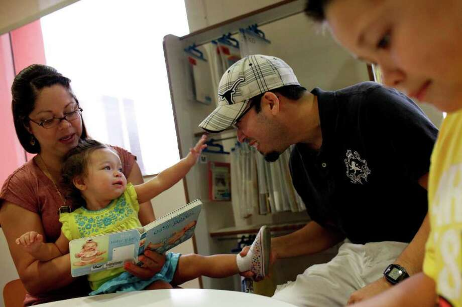 Erica Ramirez and Manny Vela flank daughter Sophia Vela and Timothy Creager, 9, at the Central Library, which had nearly 20,000 more visits last month than in July 2010. Photo: Lisa Krantz/lkrantz@express-news.net / lkrantz@express-news
