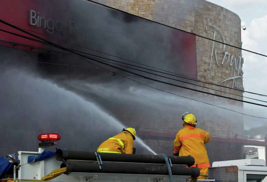 Firefighters work to extinguish a fire at the Casino Royale in Monterrey, Mexico, Thursday Aug. 25 2011. Two dozen gunmen burst into the casino in northern Mexico on Thursday, doused it with a flammable liquid and started a fire that trapped gamblers inside, killing more than 28 people and injuring a dozen more, authorities said. (AP Photo/Hans Maximo Musielik) Photo: Hans Maximo Musielik, STR / AP