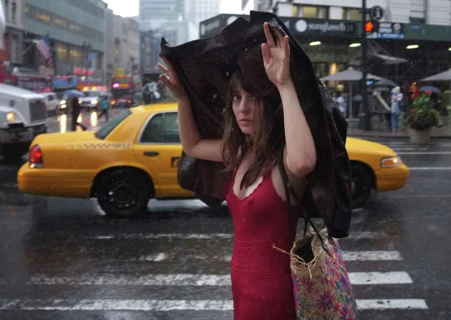 NEW YORK, NY - AUGUST 25: A woman covers her head during an afternoon shower on August 25, 2011 in New York City. New York City and much of the Eastern Seaboard is preparing for Hurricane Irene, which is expected to arrive in the metropolitan area this weekend.  (Photo by Spencer Platt/Getty Images) Photo: Spencer Platt, Getty Images / 2011 Getty Images