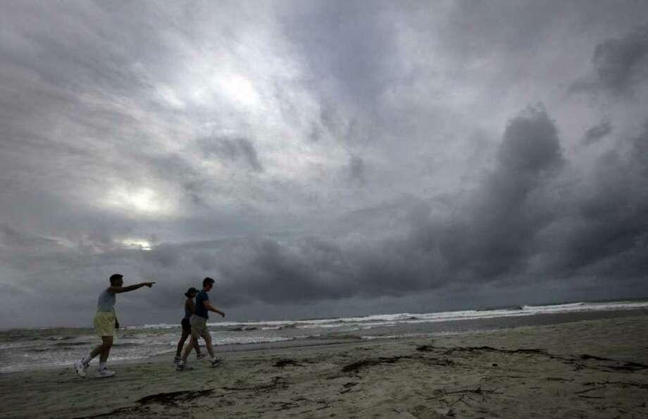 Barb Skeen señala hacia una tormenta frente a sus hija Kara Skeen y Pam Jordan mientras caminan por la playa en Pawleys Island, el viernes 26 de agosto en Carolina del Sur, mientras esperan la llegada del huracán Irene. Photo: Steve Jessmore, MBR / The Sun News