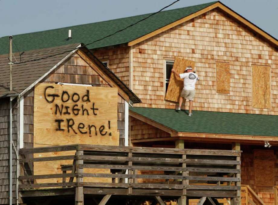 A message is left for Hurricane Irene on one house, left, as a resident boards up another in anticipation of the arrival of Hurricane Irene in Nags Head, N.C., Thursday, Aug. 25, 2011 on North Carolina's Outer Banks. (AP Photo/Charles Dharapak) Photo: Charles Dharapak, STF / AP