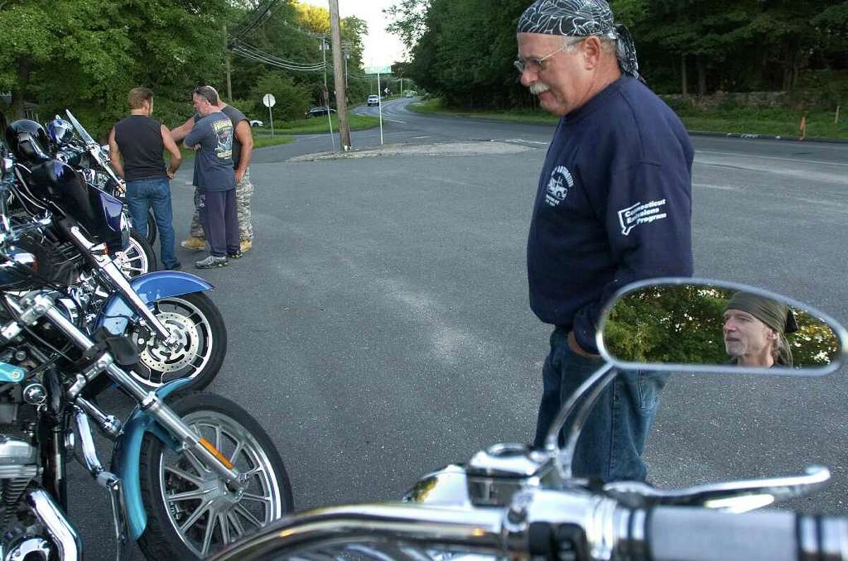 Bob Shapiro, of Stratford, and Danny Jovanelly, of Newtown, in the reflection at right, look at everybody else's ride during the weekly bike night at Hideaway Cafe on state Route 25 in Newtown on Tuesday, Aug. 23, 2011.