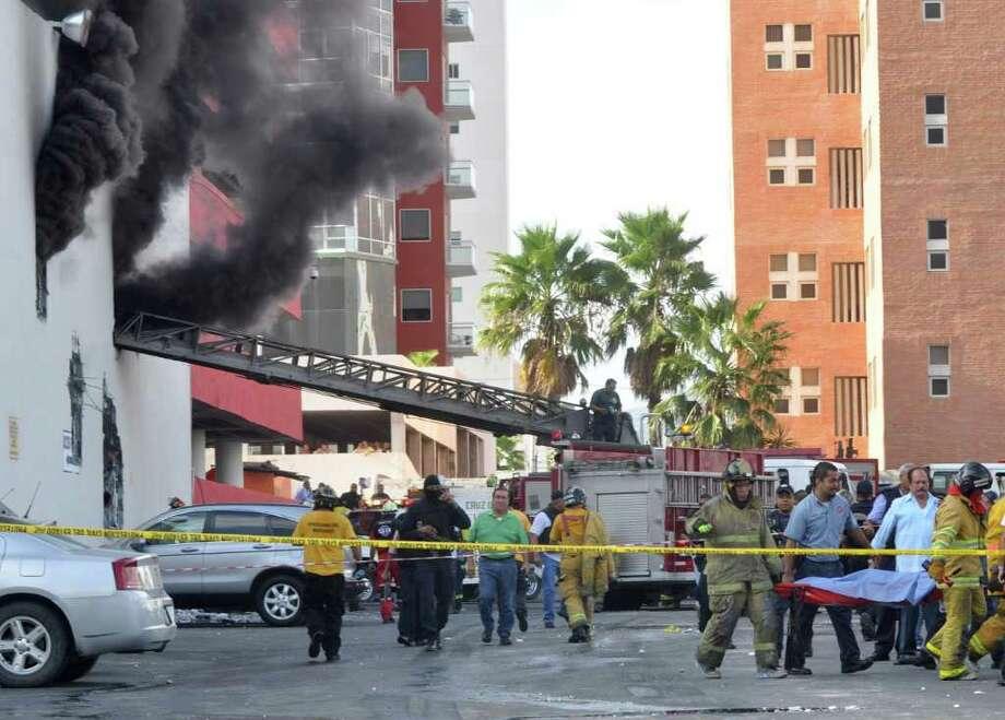 Bomberos rescatan a una persona del Casino Royale en Monterrey, México, el jueves 25 de agosto de 2011. Photo: STR / AP