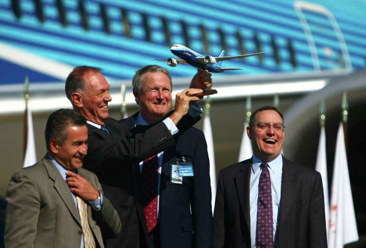 FAA Administrator Randy Babbitt holds up a model of a Boeing 787 as, from left, local FAA official Ali Bahrami, Jim Albaugh, President and CEO of Boeing Commercial Airplanes, and Scott Fancher, vice president and general manager of the 787 program celebrate during a certification ceremony for Boeing's 787 Dreamliner on Friday at Paine Field in Everett. During the event the Federal Aviation Administration certified production and flight of the aircraft.
