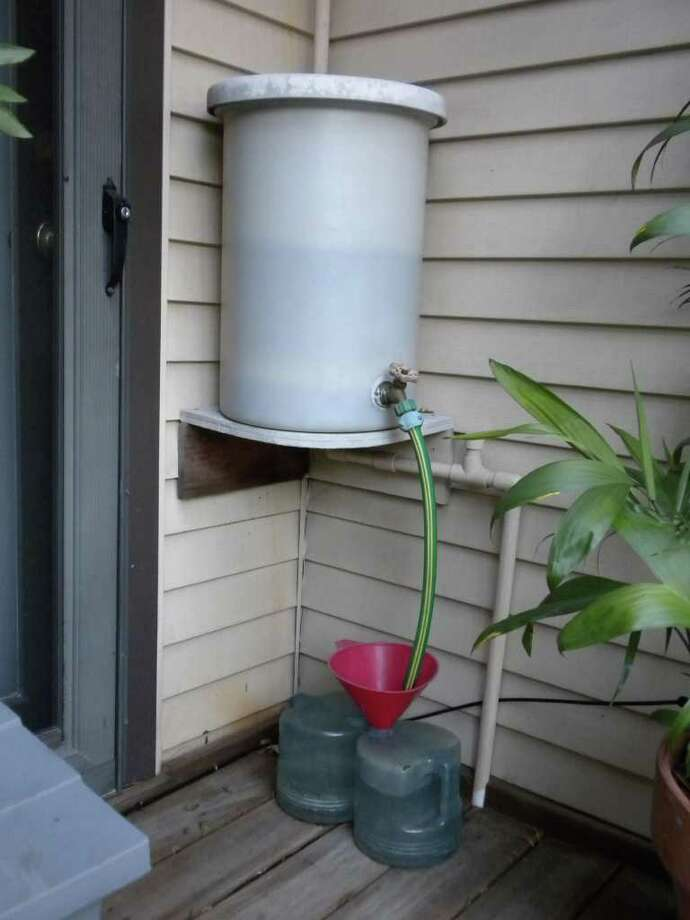 Houston Urban Gardeners founder Laurel Smith harvests AC condensate in a 10-gallon bucket. The chlorline-free water is funneled into gallon jugs used to transport water to her plants. Photo: Laurel Smith