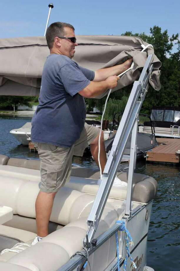 Kelly Sigrist, of New Milford, an employee of Echo Bay Marina in Brookfield, secures a boat in preparation for the hurricane expected this weekend. Photo taken Friday, August 26, 2011. Photo: Carol Kaliff