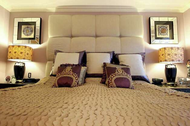 In the master bedroom, a champagne silk duvet is accented with ornate pillows, which provide contrast and hint of the more traditional elements in the room. Photo: EDWARD A. ORNELAS, SAN ANTONIO EXPRESS-NEWS / © SAN ANTONIO EXPRESS-NEWS (NFS)