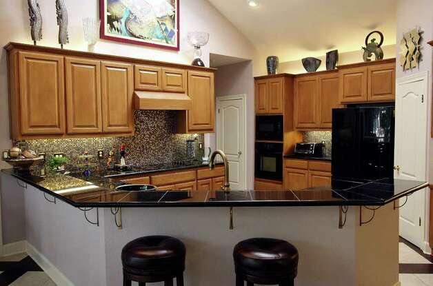 The large kitchen was among the features that attracted the couple to the home. They began its redesign by adding sleek black granite counters. Photo: EDWARD A. ORNELAS, SAN ANTONIO EXPRESS-NEWS / © SAN ANTONIO EXPRESS-NEWS (NFS)