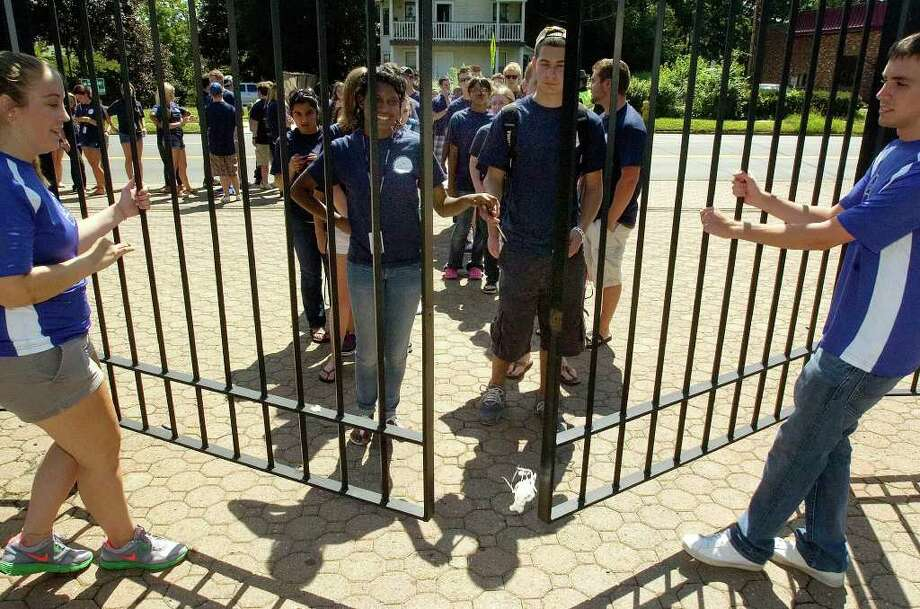 Sophomores Melissa Sobireski, left, and Matt Varrone, right, open the gates for the incoming freshmen during the traditional Entering the Gates ceremony at Western Connecticut State University's midtown campus in Danbury on Friday, Aug. 26, 2011. Photo: Jason Rearick / The News-Times