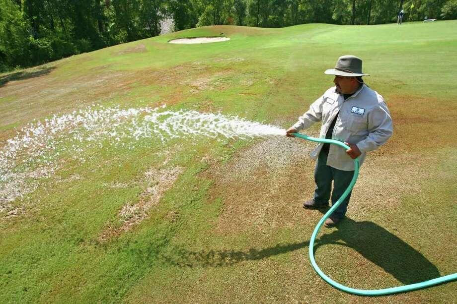 Elías Manzo, cuidador del césped de un campo de golf en The Woodlands, riega una zona deteriorada por la fuerte ola de calor que afecta a Texas. Photo: Karl Anderson, MBO / AP