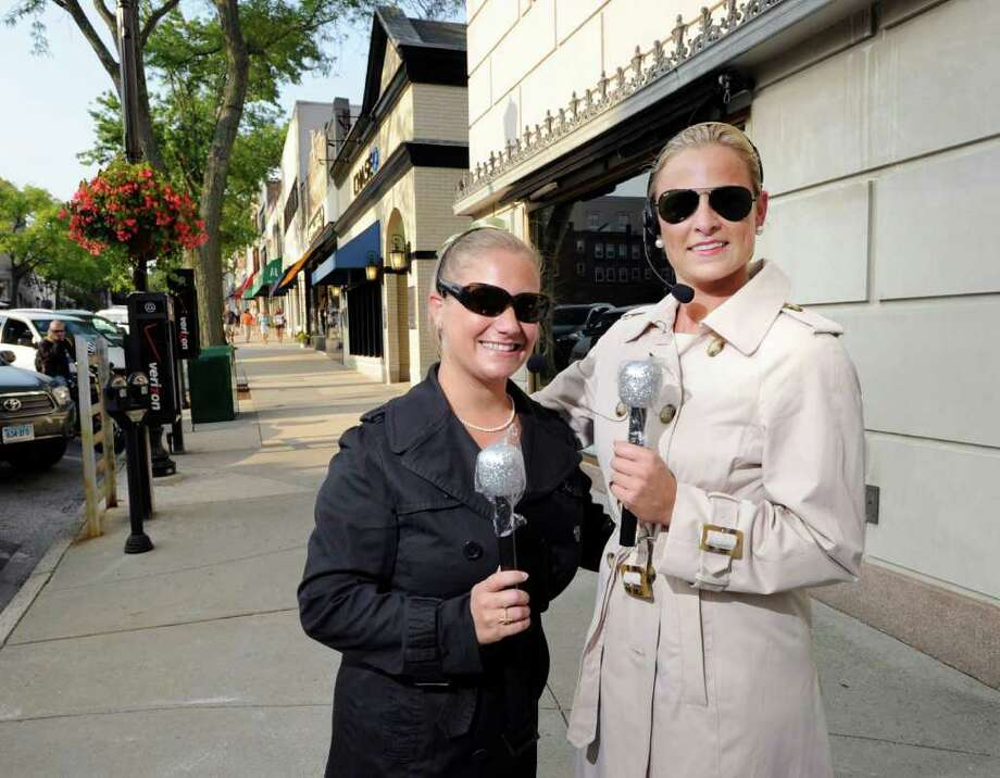 Lindsay Longmire and Laura McKittrick, left to right, pose with fake microphones on Greenwich Avenue Friday night, Aug. 26, 2011.  The pair, both Greenwich residents, have started their own Hurricane Irene blog, http://hurricaneirenect.blogspot.com. Photo: Bob Luckey / Greenwich Time