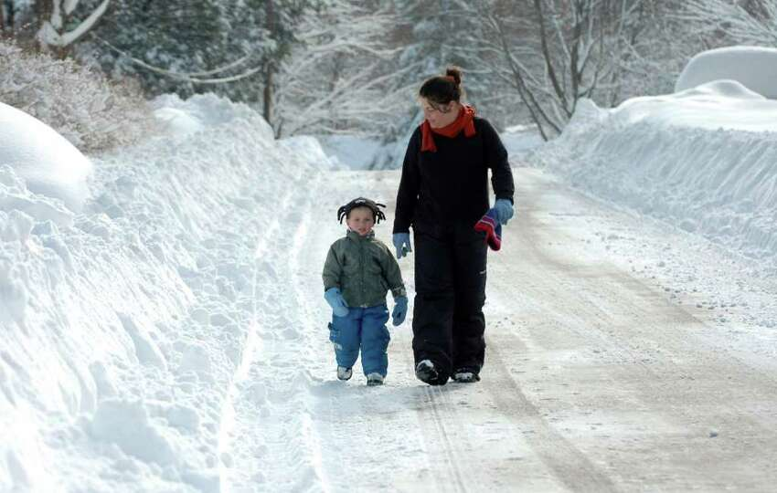 2 year-old Sean Murnin and his mom, Jessa, take a walk down a snow covered Brithwell St. in Fairfield, Conn. on Thursday, Jan. 27, 2011.