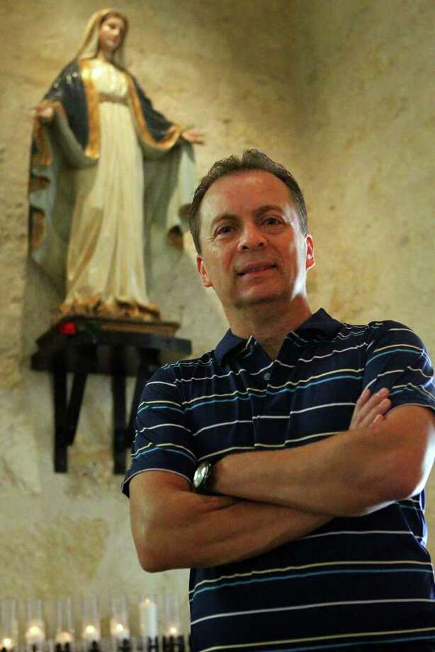 Artist Agustin Parra stands in front of one of his works called The Virgin Mary at San Fernando Cathedral. Photo: JOHN DAVENPORT, JOHN DAVENPORT/jdavenport@express-news.net / SAN ANTONIO EXPRESS-NEWS (Photo can be sold to the public)
