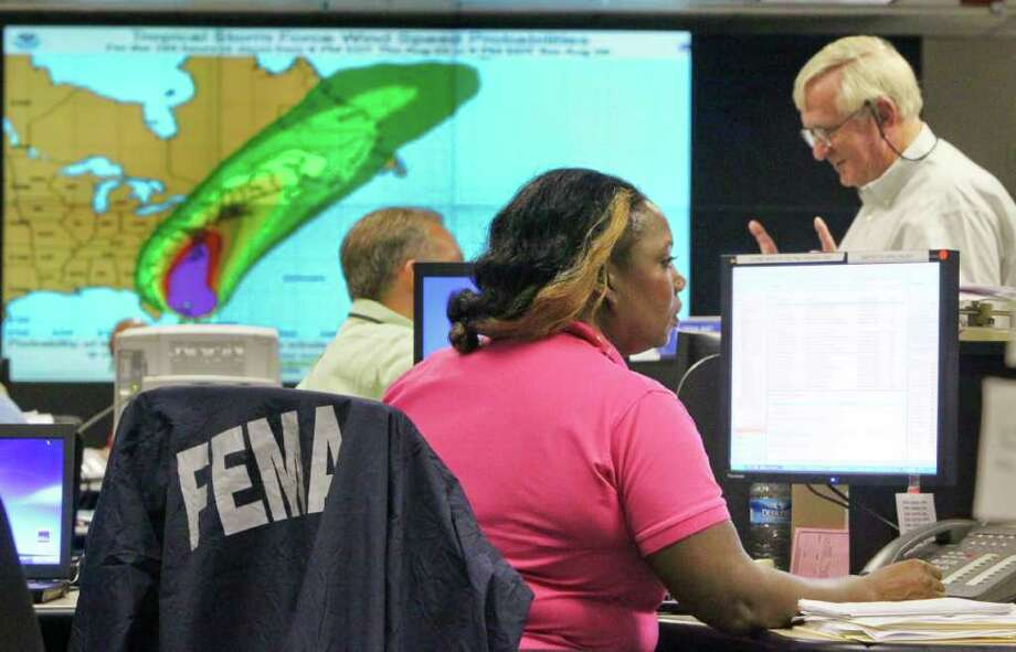 FEMA's Chandra Malcolm, left, keeps track of satellite transponder tracked trucks carrying supplies as logistic operations chief, John Southerland, right, communicates with a colleague with Hurricane Irene's position shown on a map in the background in Atlanta on Friday, Aug. 26, 2011. (AP Photo/Atlanta Journal & Constitution, John Spink) Photo: John Spink, MBO /  ©2011 Atlanta Journal Constitution