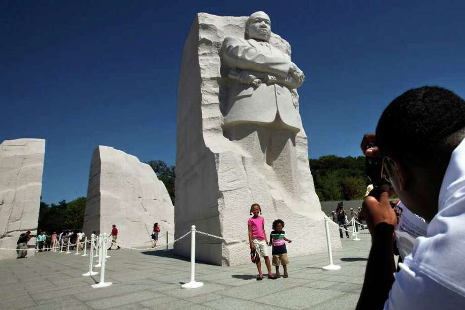 Christopher Ogden, of Charlotte, right, takes a photograph of his children, Courtney Ogden, 6, center, and Conrad Ogden, 2, with a statue of Dr. Martin Luther King, Jr. at the Martin Luther King, Jr. Memorial in Washington, Monday, Aug. 22, 2011.  The memorial will be officially dedicated on Sunday. (AP Photo/Jacquelyn Martin) Photo: Contributed Photo / The News-Times Contributed