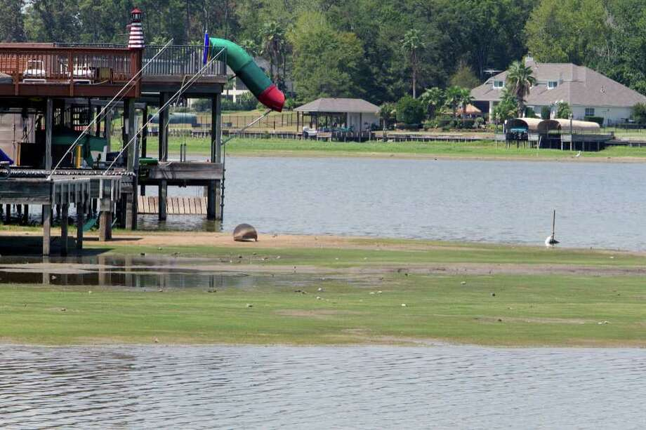 The lowering water level is visible along waterfront homes in the Cape Conroe subdivision on the shores of Lake Conroe. The lake is 4½ feet below normal levels because of the drought and the release of millions of gallons to Lake  Houston. (James Nielsen/Chronicle ) Photo: James Nielsen, Staff / © 2011 Houston Chronicle