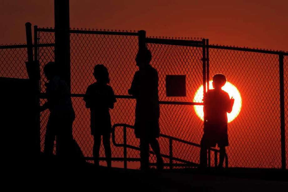 Fans watch from outside the stadium gates as the sun sets. Photo: Smiley N. Pool, Houston Chronicle / © 2011  Houston Chronicle