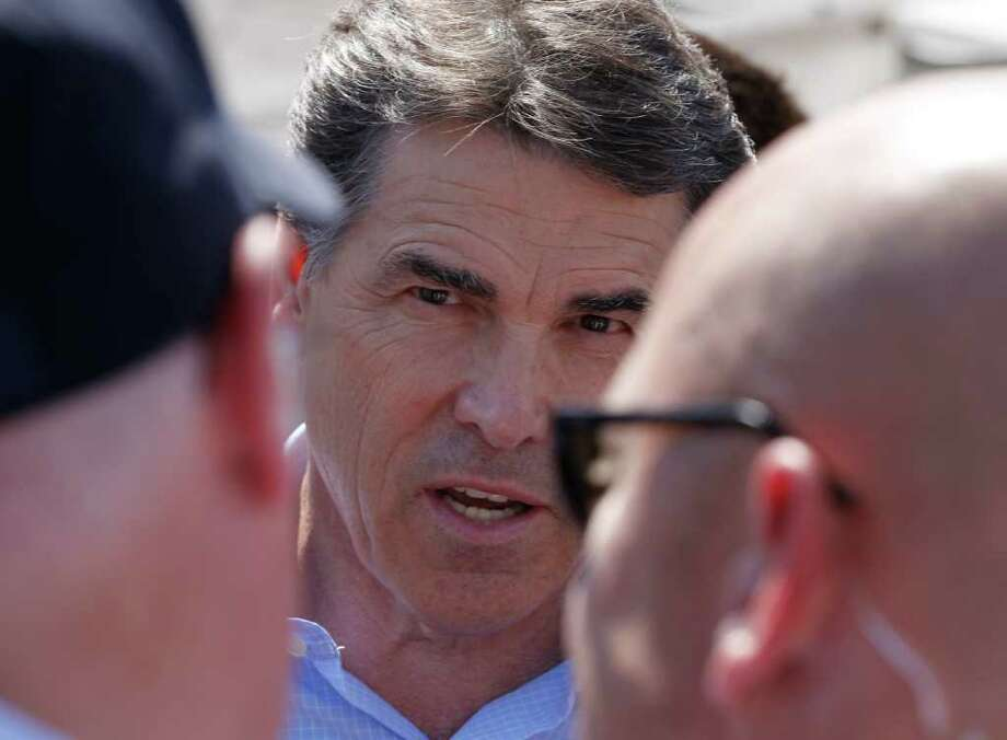 Gov. Rick Perry, shown courting voters at the Iowa State Fair in Des Moines on Aug. 15, complained the federal government is not securing the border. (AP photo) Photo: Charles Dharapak, STF / AP