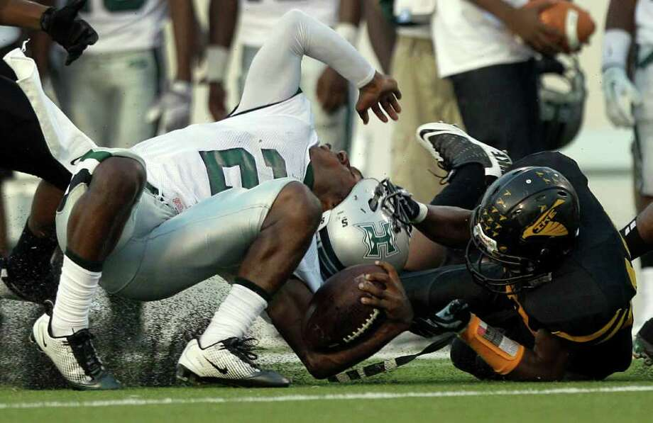 Hightower quarterback Bralon Addison (2) is pulled to the turf by his facemask by Eisenhower's Derrick Hawkins during the first quarter. Photo: Brett Coomer, Houston Chronicle / © 2011 Houston Chronicle
