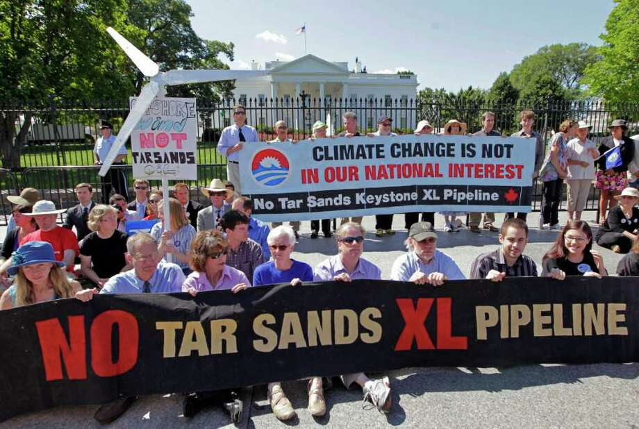 Environmental activists gather outside the White House in Washington, Monday, Aug. 22, 2011, as they continue a civil disobedience campaign against a proposed oil pipeline from Canada to the U.S. Gulf Coast, in Washington. The protesters want President Barack Obama to deny a permit for the 1,700-mile Keystone XL pipeline that would take oil extracted from tar sands in Alberta, Canada, and carry it through a pipeline cutting across Montana, South Dakota, Nebraska, Kansas, Oklahoma and Texas to refineries in Houston and Port Arthur, Texas.   (AP Photo/J. Scott Applewhite) (AP Photo/J. Scott Applewhite) Photo: J. Scott Applewhite, STF / AP