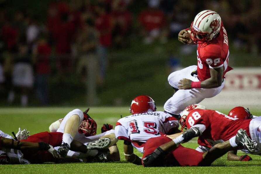Katy running back Adam Taylor tries to leap over a group of North Shore defenders during the third