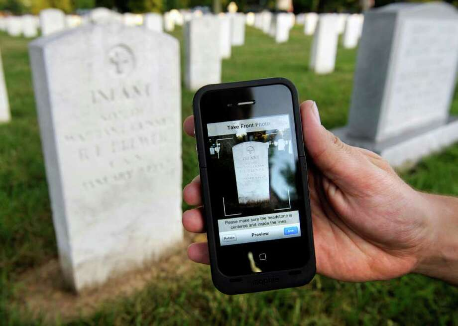 Soldiers of the Army Old Guard Task Force Christman use Apple iPhone's to photograph and catalog more than 219,00 grave markers and the front of more than 43,000 sets of cremated remains at Arlington National Cemetery in Arlington, Va., Wednesday, Aug. 24, 2011. Night after night this summer, troops have left their immaculately pressed dress blues, white gloves and shiny black boots, photographing each and every grave with an iPhone. (AP Photo/Cliff Owen) Photo: Cliff Owen, FRE / FR170079 AP