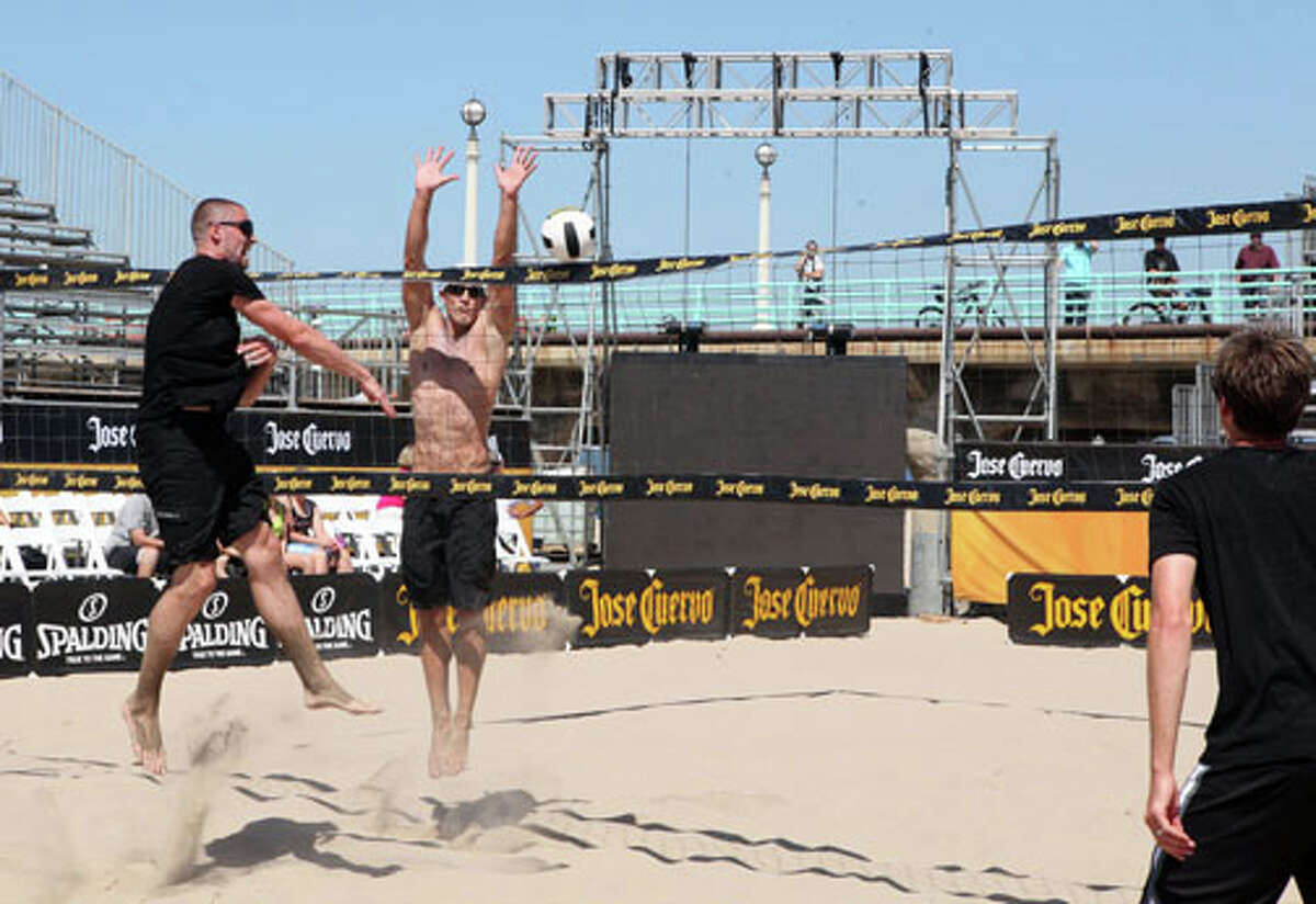 Kevin Love (left), Sean Scott (right) and Hans Stolfus (far right) compete at the first match of the Jose Cuervo Pro Beach Volleyball Series, on Thursday, August 25, 2011, in Manhattan Beach, California.