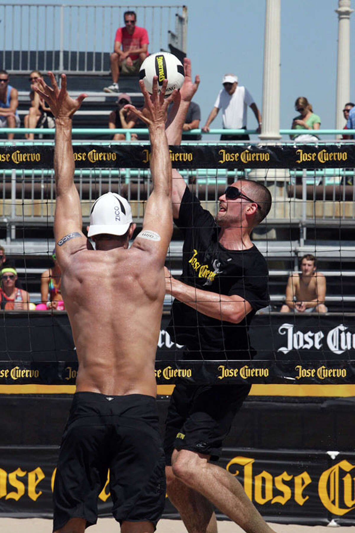 Kevin Love (right) spikes against Sean Scott (left) during the first match of the Jose Cuervo Pro Beach Volleyball Series, on Thursday, August 25, 2011, in Manhattan Beach, California.