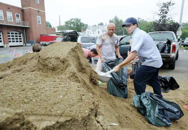 Victor Herrera, left, and Roberto Barbosa, who both work in Greenwich, fill sandbags in preparation for Hurricane Irene at the Sound Beach Fire Department in Old Greenwich, Saturday morning, Aug. 27, 2011.  Irene is expected to hit the Greenwich area sometime Sunday. Photo: Bob Luckey / Greenwich Time