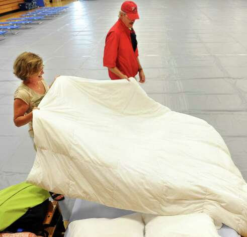 Lou Anne and Lawrence Freeman make their bed in the gym at Fairfield Ludlowe High School, the town's emergency shelter, Saturday, Aug. 27, 2011 after their road was issued a mandatory evacuation. Photo: Autumn Driscoll / Connecticut Post
