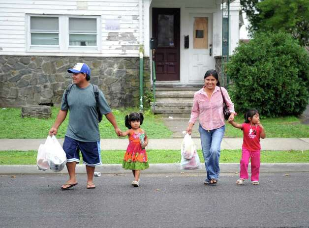 Juan Urbano and Maria Bonilla and their daughters Estelle and Victoria head to Bridgeport's emergency shelter at Bassick High School Saturday, Aug. 27, 2011 in advance of Hurricane Irene. Photo: Autumn Driscoll / Connecticut Post
