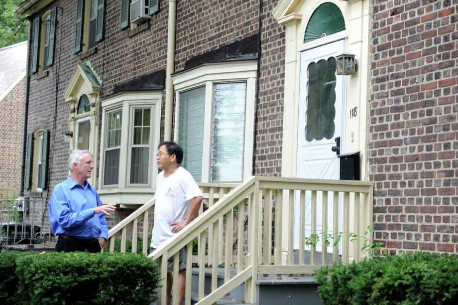 Mayor Bill Finch urges Seaside Village resident Tham Le to consider evacuating his home Saturday, Aug. 27, 2011 as Hurricane Irene bears down on Bridgeport. Photo: Autumn Driscoll / Connecticut Post