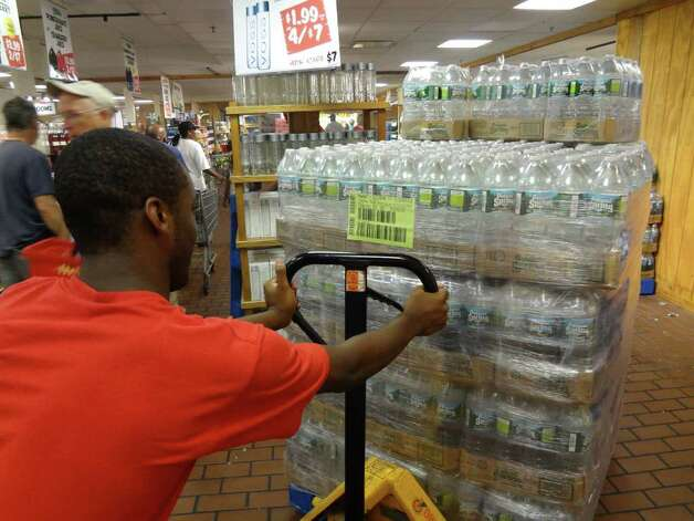 Stew Leonard's employee Seneque Bruneus restocks the water supply on Saturday, August 27, 2011. Photo: Ralph Filardo / Hearst CT Media Group