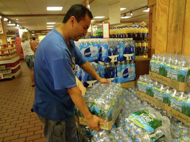 Norwalk resident Abdias Rosas picks up a case of water at Stew Leonard's in preparation for Hurricane Irene on Saturday, August 27, 2011. Photo: Ralph Filardo / Hearst CT Media Group