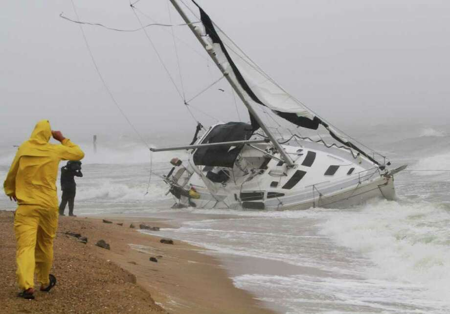 A stranded sailboat founders in the surf along the Willoughby Spit area of Norfolk, Va. as Hurricane Irene hits Norfolk, Va., Saturday, Aug. 27, 2011. The live-aboard couple attempted to outrun the storm and got caught up in the high surf and wind. They were rescued by local fire and rescue personnel.  (AP Photo/Steve Helber) Photo: Steve Helber, STF / AP