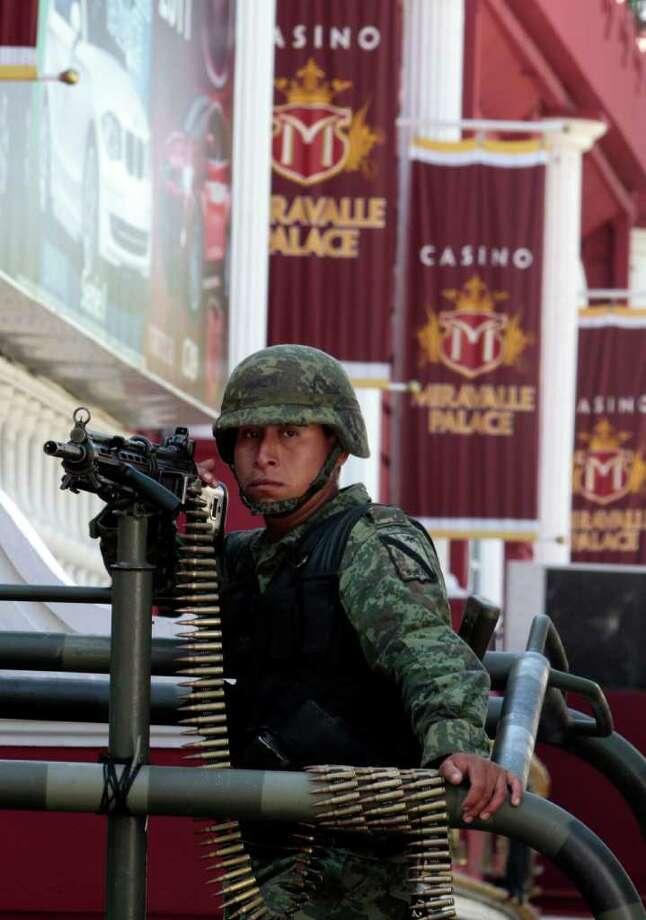 A soldier holds a machine gun outside a casino in Monterrey, Mexico, Saturday, Aug. 27, 2011. According to an official of Mexico's Attorney General's Office  soldiers and federal agents have confiscated hundreds of slot machines at five casinos in Monterrey. A surveillance tape showed eight or nine men arriving in four cars Thursday at the Casino Royale in Monterrey and setting fire to the building, trapping dozens of people inside and killing at least 52 people. (AP Photo/Arnulfo Franco) Photo: Arnulfo Franco, STF / AP
