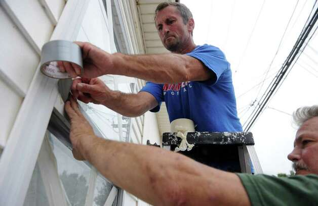 Tom Francoeur places tape on his windows with some help from friend Daniel Gallagher along Broadway in Milford, Conn. on Saturday August 27, 2011. Photo: Christian Abraham / Connecticut Post